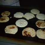 Here you can see a few Pupusas on the stove being cooked. Some are almost ready and some were just put on there.