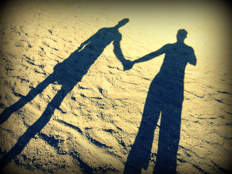 Hold hands shadow on the beach